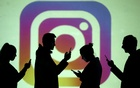 Silhouettes of mobile users are seen next to a screen projection of Instagram logo in this picture illustration taken March 28, 2018. REUTERS/Dado Ruvic/Illustration