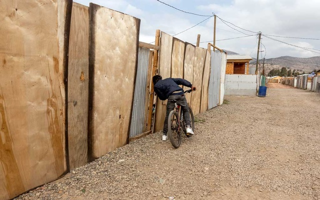 Jean Stivens, a Haitian migrant, peeks inside a friend's home at a migrant camp in Lampa, Chile, on Sept 22, 2021. Many of the Haitian migrants who recently entered Texas had taken refuge for years in Chile. Cristobal Olivares/The New York Times