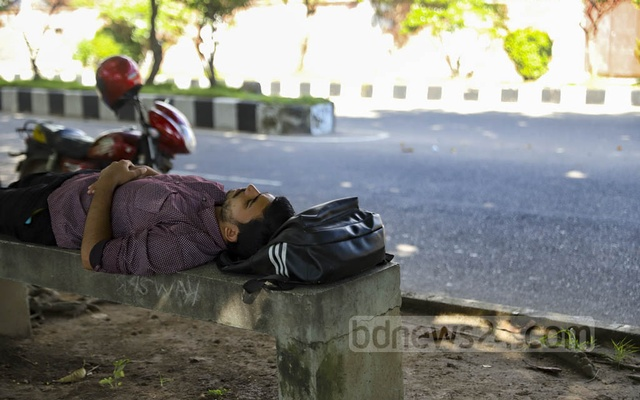 An exhausted rider parks his motorcycle to take a rest on a bench at Hatirjheel in Dhaka on Thursday, Sep 30, 2021. Photo: Mahmud Zaman Ovi