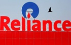 A bird flies past a Reliance Industries logo installed on its mart in Ahmedabad, India January 16, 2017. REUTERS