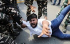 Police forces detain a man during a protest by activists of the youth wing of India's main opposition Congress party outside UP Bhawan, after people were killed when violence broke out in Uttar Pradesh state on Sunday, when a car linked to a federal minister ran over farmers taking part in a protest against controversial farm laws, in New Delhi, India, October 4, 2021. REUTERS/Anushree Fadnavis