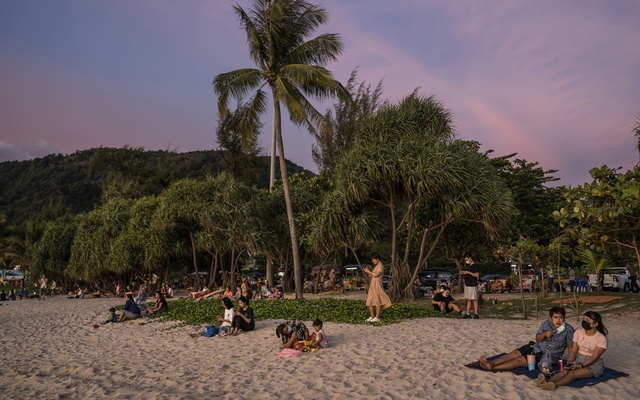 People watch the sunset on the beach in Patong, Phuket, Thailand, Oct 3, 2021. The New York Times