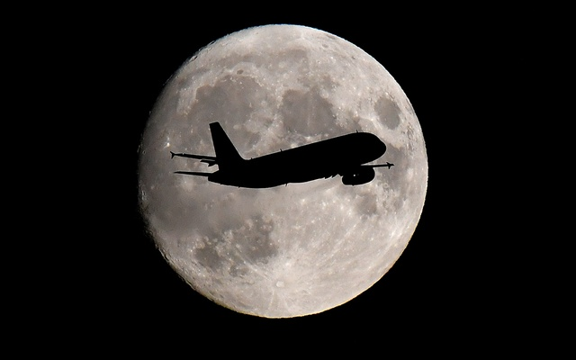 A passenger plane passes in front of the moon as it makes its final landing approach to Heathrow Airport in London, Britain September 12, 2019. REUTERS