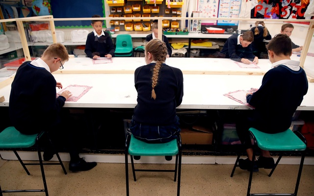 Children sit in a classroom on their first day of school at Heath Mount, amid the outbreak of the coronavirus disease (COVID-19), in Watton at Stone, Britain September 3, 2020. REUTERS