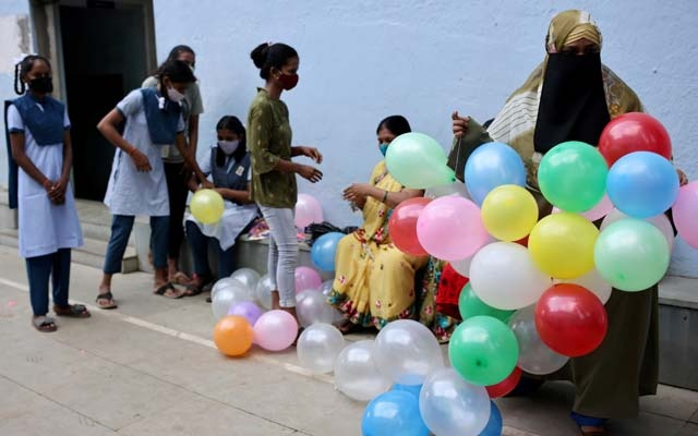 Students and teachers prepare to decorate a school following the reopening after over a year due to the coronavirus disease (COVID-19) pandemic in Mumbai, India, October 4, 2021. REUTERS
