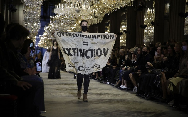 """A climate activist, bearing a white banner with the words """"Overconsumption = Extinction"""" in bold block lettering, crashes the runway at the Louis Vuitton spring 2022 fashion show at the Louvre Museum in Paris, Oct 5, 2021. It wasn't the first time a protester has appeared at Paris Fashion Week, and the environmental organization Extinction Rebellion says it won't be the last. (Valerio Mezzanotti/The New York Times)"""