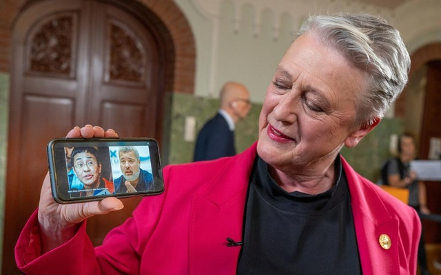 Chair of the Norwegian Nobel Peace Prize Committee Berit Reiss-Andersen shows on a mobile phone laureates of the 2021 Nobel Peace Prize, journalists Maria Ressa and Dmitry Muratov, in the Nobel Institute in Oslo, Norway Oct 8, 2021. NTB/Heiko Junge via REUTERS