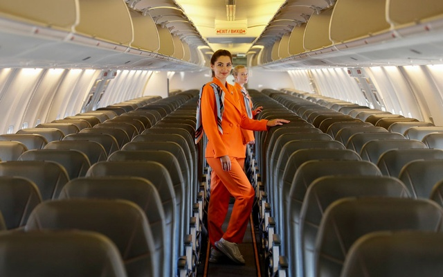 Flight attendants of SkyUp Airlines pose for a picture on board a plane during the presentation of a new uniform at the Boryspil International Airport outside Kyiv, Ukraine September 30, 2021. The Ukrainian low-cost airline presented their innovative uniform, including loose costumes and sneakers, for the crew to feel comfortable and look fashionable during the flights. REUTERS