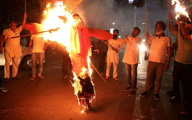 Protestors burn an effigy of Yogi Adityanath, Chief Minister of the northern state of Uttar Pradesh, during a protest after people were killed when a car linked to a federal minister ran over farmers protesting against controversial farm laws in Uttar Pradesh on Sunday, in Kolkata, India, Oct 4, 2021. REUTERS/Rupak De Chowdhuri