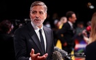 Director George Clooney speaks to the media as he arrives for a screening of the film