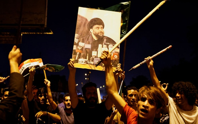 A man holds up a picture of Shi'ite cleric Moqtada al-Sadr, as supporters of Sadr's movement celebrate after preliminary results of Iraq's parliamentary election were announced in Baghdad, Iraq October 11, 2021. REUTERS/Thaier Al-Sudani