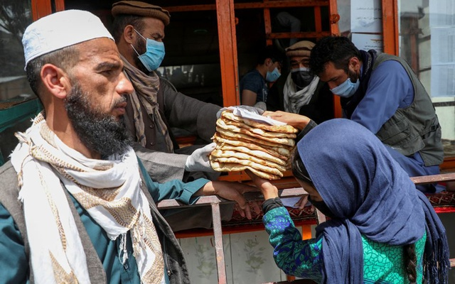 An Afghan girl receives free bread distributed by the government, outside a bakery, during the COVID-19 outbreak in Kabul, Afghanistan May 3, 2020. REUTERS