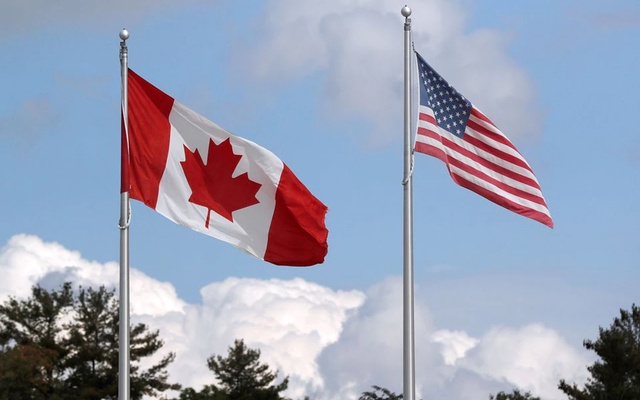 A US and a Canadian flag flutter at the Canada-United States border crossing at the Thousand Islands Bridge, which remains closed to non-essential traffic to combat the spread of the coronavirus disease (COVID-19) in Lansdowne, Ontario, Canada September 28, 2020. REUTERS.