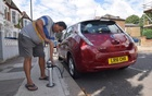 Uber driver Tim Win demonstrates plugging his fully-electric Nissan Leaf into an on-street residential electric vehicle charging system developed by startup Trojan Energy in London, Britain, August 2, 2021. REUTERS