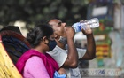 A rickshaw passenger drinks water from a bottle amid the sweltering heat at Shahbagh in Dhaka on Wednesday, Oct 13, 2021. Photo: Mahmud Zaman Ovi