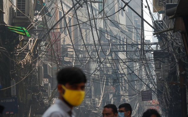 A man walks under power cables in an alley in the old quarters of Delhi, India, February 1, 2021. REUTERS