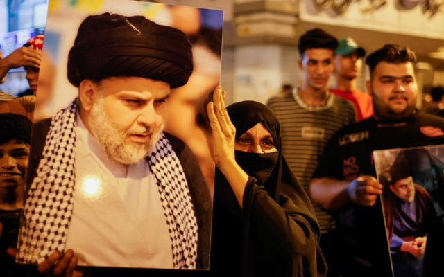 A woman holds a picture of Sadr's movement leader Moqtada al-Sadr, as his supporters celebrate after preliminary results of Iraq's parliamentary election were announced in Baghdad, Iraq October 11, 2021. REUTERS/Thaier Al-Sudani