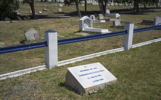 """A mass grave with a stone that says """"In memory of the migrants who died in the waters of the Strait"""" at the cemetery in Tarifa, Spain, June 24, 2021."""