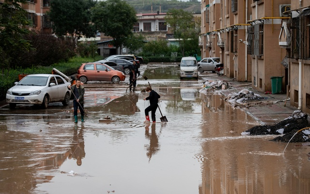 Villagers clear floodwaters near residential houses following heavy rainfall in Yitang county, Jiexiu city, Shanxi province, China October 10, 2021. Picture taken October 10, 2021. cnsphoto via REUTERS