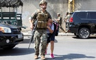 An army soldier helps a schoolgirl get to her parents, after gunfire erupted in Beirut, Lebanon October 14, 2021. Reuters