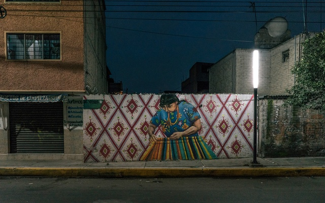 A mural of an indigenous, lit by a streetlight, on a wall in the sprawling borough of Iztapalapa, Sept. 13, 2021. The murals, which include both local heroes and icons like Frida Kahlo, are part of the Izatapalapa mayor's art initiative and a broader plan to make the impoverished, high crime area safer. (Luis Antonio Rojas/The New York Times)