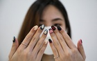 A customer shows her Squid Game's manicure at the nail salon Maniqure in Kuala Lumpur, Malaysia Oct 14, 2021. REUTERS