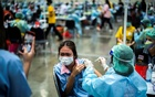 A high school student receives the first dose of Pfizer-BioNTech vaccine against the coronavirus disease (COVID-19) ahead of schools reopening in November, at a convention hall in the outskirts of Bangkok, Thailand, Oct 15, 2021. REUTERS/Athit Perawongmetha