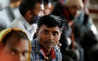 Indian migrant workers wait inside a railway station to board trains to their home states following attacks on migrant labourers by suspected militants in Kashmir, on the outskirts of Srinagar Oct 18, 2021. REUTERS/Danish Ismail