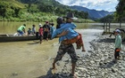 A refugee carries his grandmother to the shore of Mizoram, India, after crossing the Tiau River from Myanmar, Oct 14, 2021. For decades, armed conflict, political repression and targeted campaigns against minorities have forced hundreds of thousands of people to leave the country. Now many more are expected to follow. (Atul Loke/The New York Times)