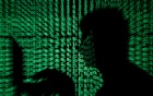 A man holds a laptop computer as cyber code is projected on him in this illustration picture taken on May 13, 2017. REUTERS