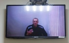Russian opposition leader Alexei Navalny is seen on a screen via a video link during a hearing to consider his lawsuits against the penal colony over detention conditions there, at the Petushki district court in Petushki, Russia May 26, 2021. REUTERS/Maxim Shemetov