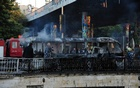 Civil defence members put out a bus fire at the site of a roadside bomb attack in central Damascus, Syria, in this handout released by SANA October 20, 2021. SANA via REUTERS