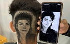 Barber brothers Rajwinder Singh Sidhu, 29, and Gurwinder Singh Sidhu, 31, make a haircut tattoo of Michael Jackson in a customer's hair inside their shop in Dabwali town, in the northern state of Punjab, India, Oct 11, 2021. REUTERS