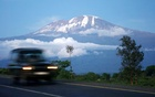 A vehicle drives past Mount Kilimanjaro in Tanzania's Hie district Dec 10, 2009. At the foot of Africa's snow-capped Mount Kilimanjaro, images of the mountain adorn the sides of rusting zinc shacks and beer bottle labels, but the fate of the real version hangs in the balance. REUTERS/Katrina Manson