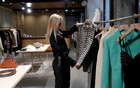A shop assistant looks clothes by the Hungarian luxury brand Nanushka are seen in the Nanushka store in Budapest, Hungary, October 14, 2021. REUTERS