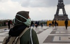 A woman, wearing a hijab and a protective face mask, walks at Trocadero square near the Eiffel Tower in Paris, France, May 2, 2021. Picture taken on May 2, 2021. REUTERS