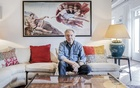 """Renato Casaro, whose hand-drawn art for movie posters has hooked audiences around the world since the 1950s, at home with one of his works, """"The Touch,"""" in Treviso, Italy, Oct. 5, 2021. The largely unknown, uncredited maestro of film posters is getting his moment in the limelight through an ambitious retrospective: """"Renato Casaro. Cinema's Last Poster Designer. Treviso, Rome, Hollywood."""" (Alessandro Grassani/The New York Times)"""