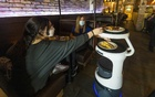 A Servi robot brings customers their food at Sergio's Restaurant in Miami, Oct 6, 2021. Servi uses cameras and laser sensors to carry plates of food from the kitchen to tables in the dining room, where the waiter then transfers the plates to the customer's table. Saul Martinez/The New York Times