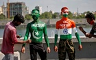 Cricket fans pose as get their bodies painted with the Indian and Pakistani national flag colours, ahead of the first match between India and Pakistan in Twenty20 World Cup super 12 stage in Dubai, in Ahmedabad, India, October 23, 2021. REUTERS