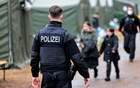 Police officers escort migrants at a camp in Eisenhuettenstadt, Germany, October 14, 2021. Reuters