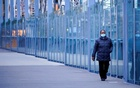 A woman wearing a protective face mask walks along a deserted city bridge during a lockdown as the state of Victoria looks to curb the spread of a COVID-19 outbreak in Melbourne, Australia, July 16, 2021. REUTERS