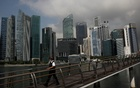 A man passes the city skyline during the coronavirus disease (COVID-19) outbreak, in Singapore, Sept 29, 2021. REUTERS/Edgar Su