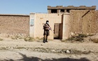 A Taliban solider stands guard in front of a house neighbouring the Islamic State hideout raided by Taliban forces on Sunday night in northern Kabul, Afghanistan Oct 4, 2021. REUTERS