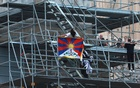 A protester holds a Tibetan flag during a demonstration at the Acropolis Propylaea, in Athens, Greece, October 17, 2021. REUTERS/Elias Marcou/File