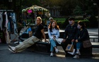 People sit in Manhattan's Washington Square Park on Oct 12, 2021. COVID cases have been falling in every region of the US, offering hope. Gabriela Bhaskar/The New York Times