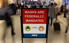 Air travelers make their way past a sign mandating face masks for all during the outbreak of the coronavirus disease (COVID-19) at Phoenix international airport in Phoenix, Arizona, US September 24, 2021. REUTERS